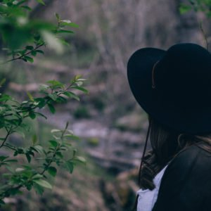 Woman with black hat looks to a wood symbolising law of attraction visualising