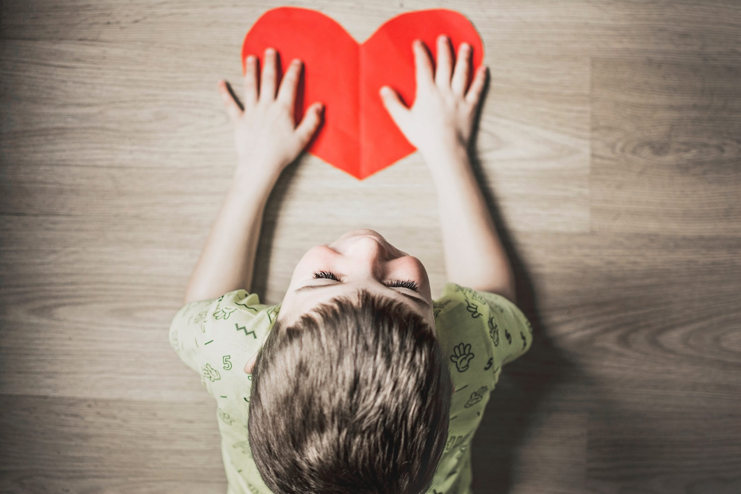 boy with cut-out paper heart on wooden floor