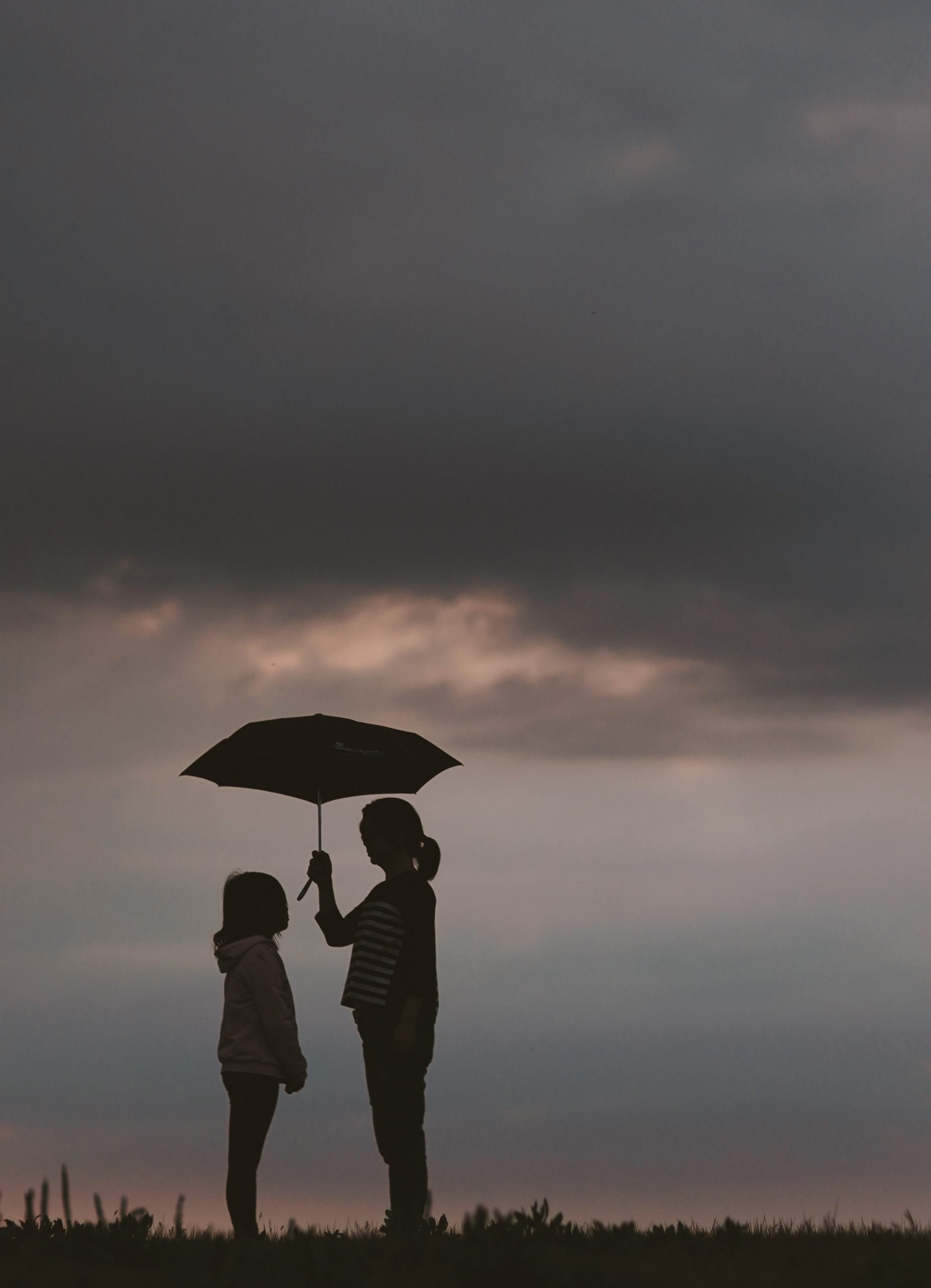 Mom holds umbrella over daughter
